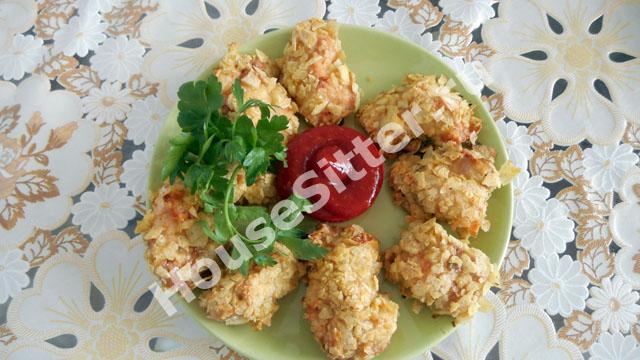Готовые наггетсы на тарелке с соусом и зеленью